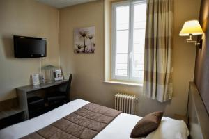 A bed or beds in a room at Brit Hotel Le Surcouf