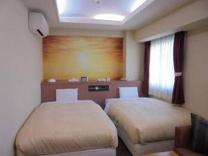 A bed or beds in a room at Spa & Sauna Hotel Hitachi Plaza