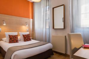 A bed or beds in a room at Hôtel Edmond Rostand