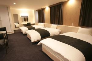 A bed or beds in a room at Miyazaki Daiichi Hotel