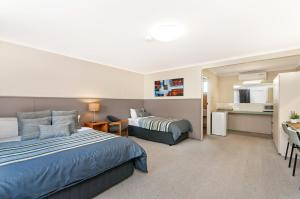 A bed or beds in a room at Melaleuca Motel