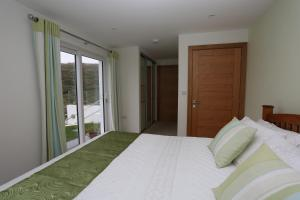 A bed or beds in a room at Holywell Bay B & B