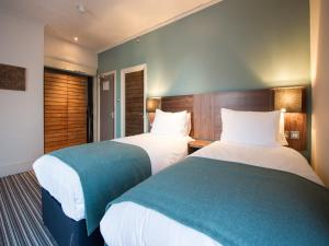 A bed or beds in a room at Innkeeper's Lodge Godalming
