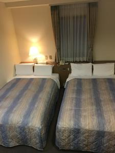 A bed or beds in a room at Hotel Crown Hills Matsuyama