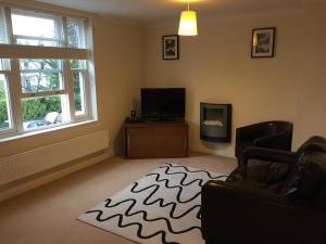 A television and/or entertainment center at Leamington Spa Serviced Apartments - Avon Croft