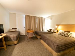 A bed or beds in a room at Posthouse Motor Lodge