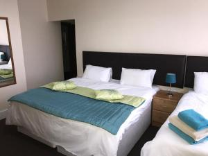 A bed or beds in a room at Acorn Lodge Guest House