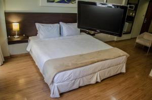 A bed or beds in a room at Mont Blanc Apart Hotel - Duque de Caxias