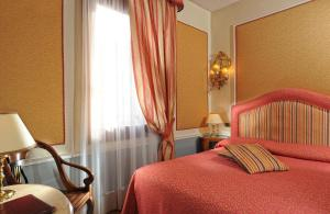 A bed or beds in a room at Hotel Arlecchino