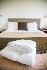 A bed or beds in a room at Lilac City Motor Inn & Steakhouse