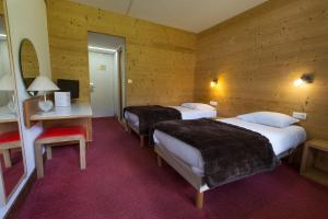 A bed or beds in a room at Hotel Le Druos