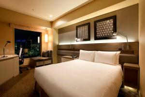 A bed or beds in a room at The Royal Park Hotel Iconic Tokyo Shiodome