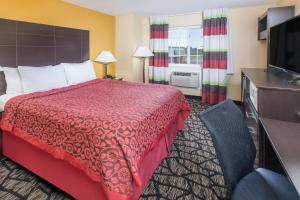 A bed or beds in a room at Days Inn by Wyndham Miami