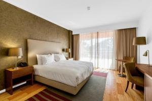 A bed or beds in a room at Vilamoura Garden Hotel