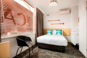 A bed or beds in a room at Nightcap at Caringbah Hotel