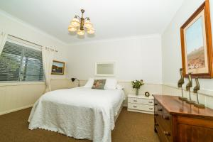 A bed or beds in a room at The Cottage at The Bryn at Tilba