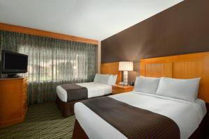 A bed or beds in a room at DoubleTree Suites by Hilton Orlando at Disney Springs