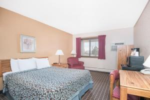 A bed or beds in a room at Days Inn by Wyndham Sioux Falls Airport