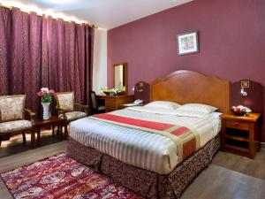 A bed or beds in a room at Safeer Hotel Suites
