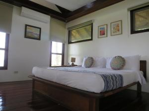 A bed or beds in a room at Sandy Feet Siargao