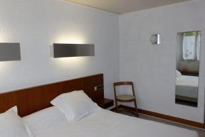 A bed or beds in a room at Hôtel le Relais