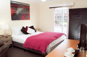 A bed or beds in a room at The Mews Motel