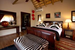 A bed or beds in a room at Umzolozolo Private Safari Lodge & Spa