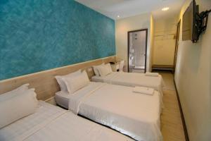 A bed or beds in a room at Pantai Inn Kota Kinabalu