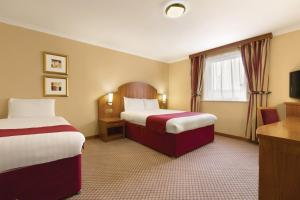 A bed or beds in a room at Ramada London Ruislip