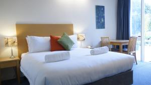 A bed or beds in a room at Parkwood Motel & Apartments