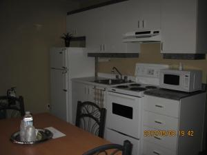 A kitchen or kitchenette at Motel Parc Beaumont Inc.