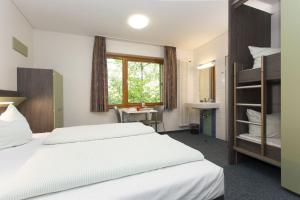A bed or beds in a room at Jugendherberge Aachen