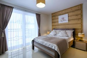 A bed or beds in a room at Gordonówka Apartamenty & SPA