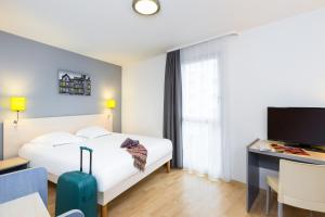 A bed or beds in a room at Aparthotel Adagio Access Rennes Centre