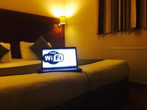 A bed or beds in a room at Stockwood Hotel - Luton Airport
