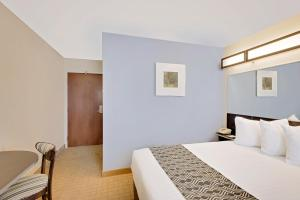 A bed or beds in a room at Microtel Inn and Suites by Wyndham - Geneva
