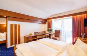 A bed or beds in a room at Sporthotel Pechtl