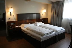 A bed or beds in a room at Dürer-Hotel