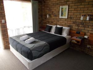 A bed or beds in a room at Park House Motor Inn