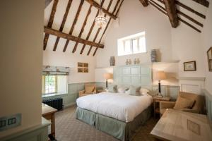A bed or beds in a room at Buckland Manor - A Relais & Chateaux Hotel