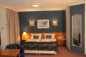 A bed or beds in a room at Grunau Hotel