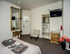 A bed or beds in a room at Riverside Guest House