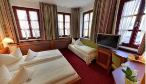 A bed or beds in a room at Hotel Augsburger Hof