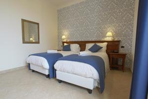 A bed or beds in a room at Relais Villa Giuliana
