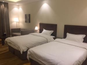 Cama ou camas em um quarto em Asfar Plaza