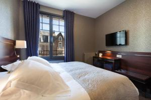 A bed or beds in a room at Hotel Ambassadeurs