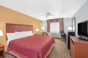 A bed or beds in a room at Days Inn by Wyndham Lamar