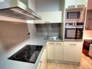 A kitchen or kitchenette at Tamarit Apartments
