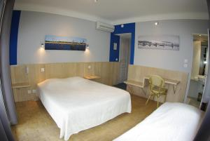 A bed or beds in a room at Hotel L'Ecureuil