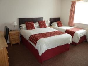 A bed or beds in a room at The Winsford Lodge